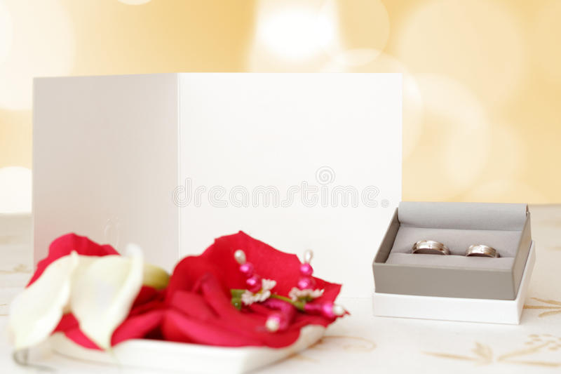 Wedding announcement with rings and space for text, focus wedding anouncement, blurred rings, focus to white paper with space fo royalty free stock photos