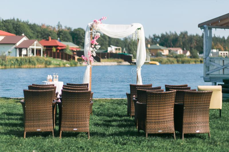 The wedding arc is decorated with flowers at the wedding ceremony. Front view through armchairs. Lake on background royalty free stock photos