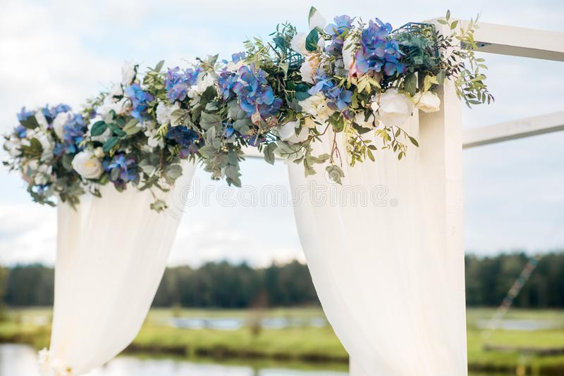 The Wedding Arch Is Decorated With Blue Flowers And White