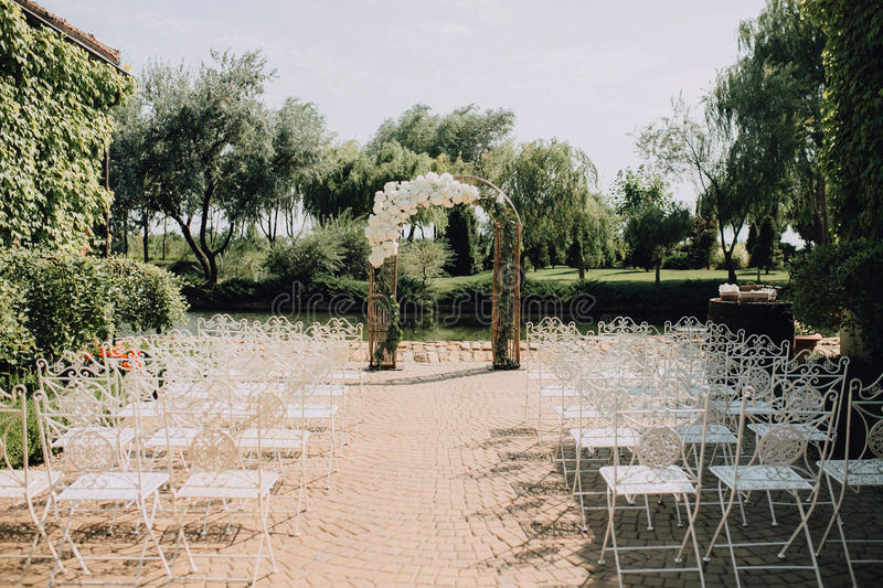 Wedding arch and vintage white chairs at a ceremony in a summer park royalty free stock photo