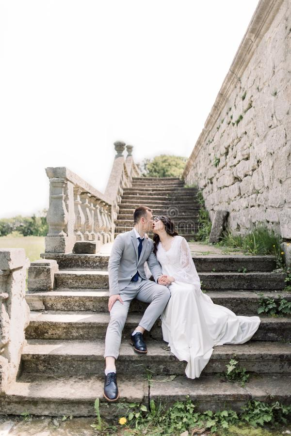 Wedding, Asian groom and bride holding hands, while sitting on the ancient stone stairs, next to old castle. Romantic royalty free stock photography