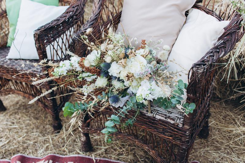 Wedding asymmetrical stylish bouquet with roses on a boho wicker chair. stock image