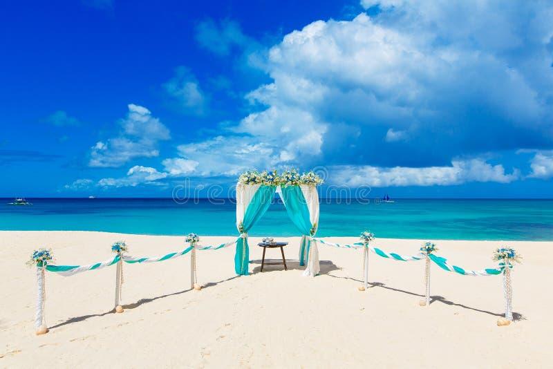 Wedding auf dem Strand Hochzeitsbogen verziert mit Blumen auf tr stockbild