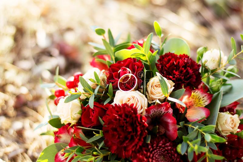 Wedding background bouquet and rings.The bride`s bouquet of red and pink flowers and greenery, with a ribbon of color Marsala. stock photography
