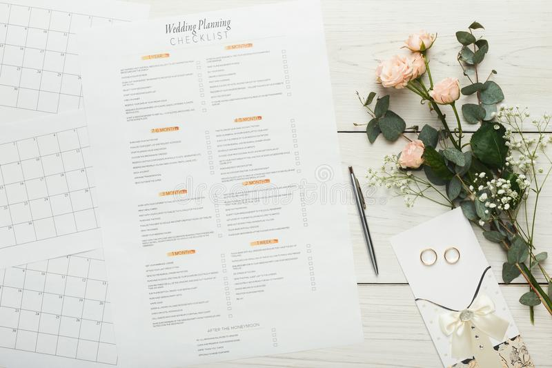 Bridal background with planner checklist. Wedding background with checklist. Paper planner and wedding rings on white wooden table with tender bridal bouquet royalty free stock photo