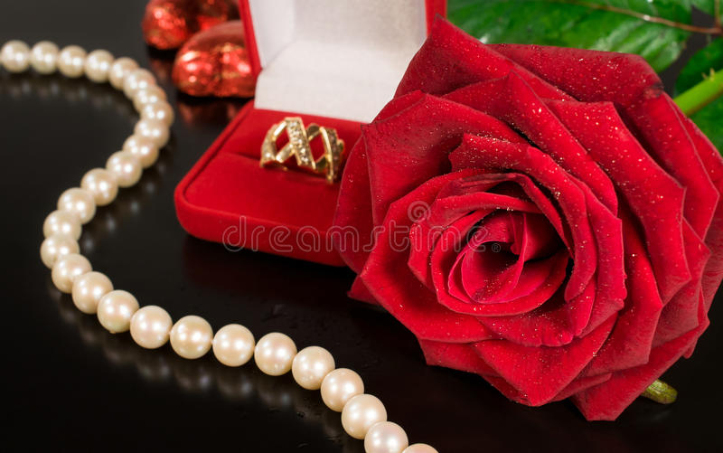 Wedding background .Rose , pearls and a gold ring. On a black background stock photos