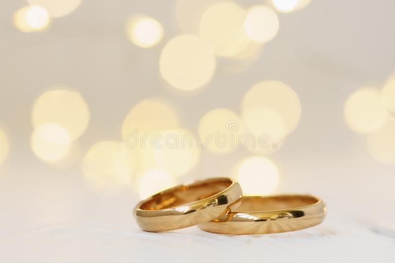 Wedding background with two golden rings stock photography