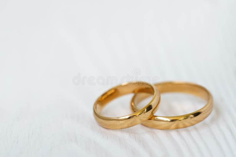 Wedding background with two rings on white wood stock photos