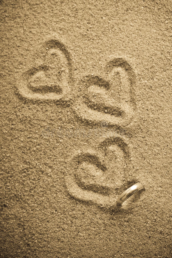 Wedding Band in Sand. With Trail of Hearts stock photo