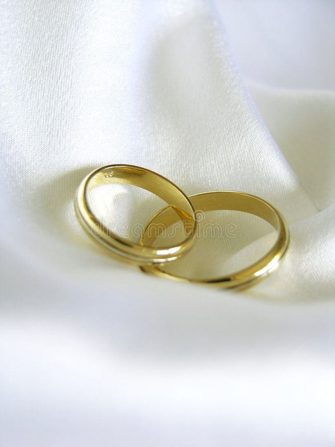 Wedding bands. Two gold wedding bands on white satin