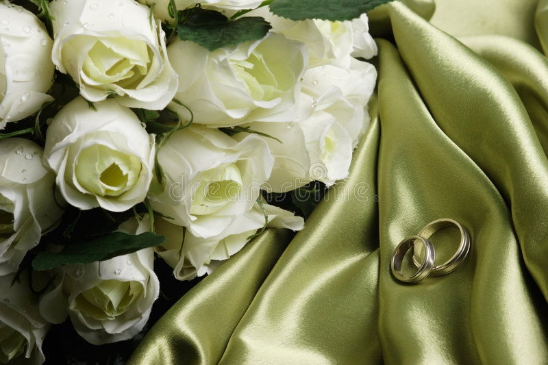 Wedding bands on green satin royalty free stock photo