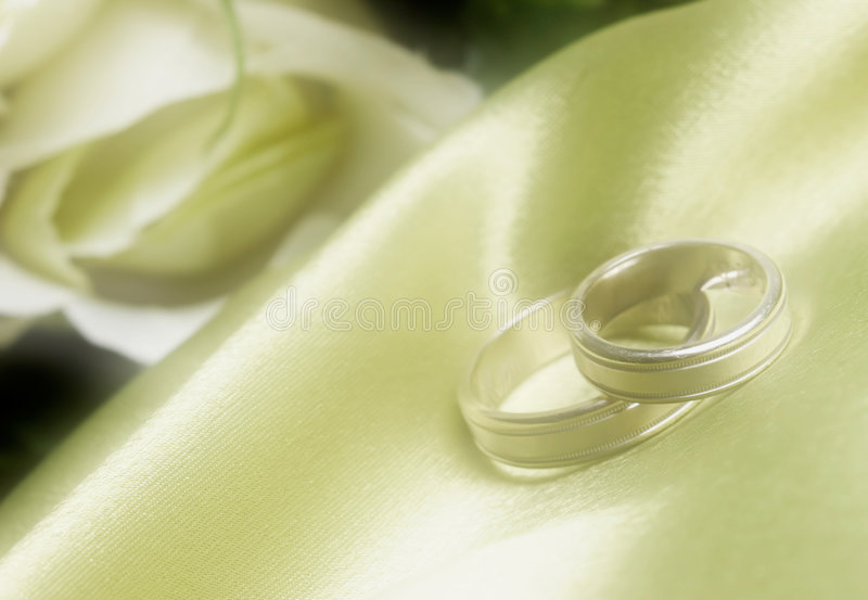 Wedding bands on green satin in dreamy stock images