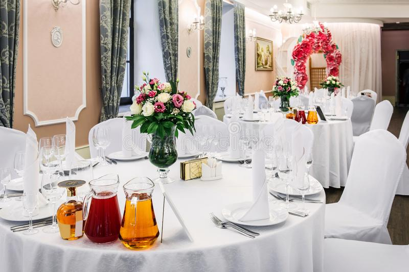 Wedding. Banquet. Round table for guests, served with cutlery, flowers and crockery and covered with a tablecloth royalty free stock photo