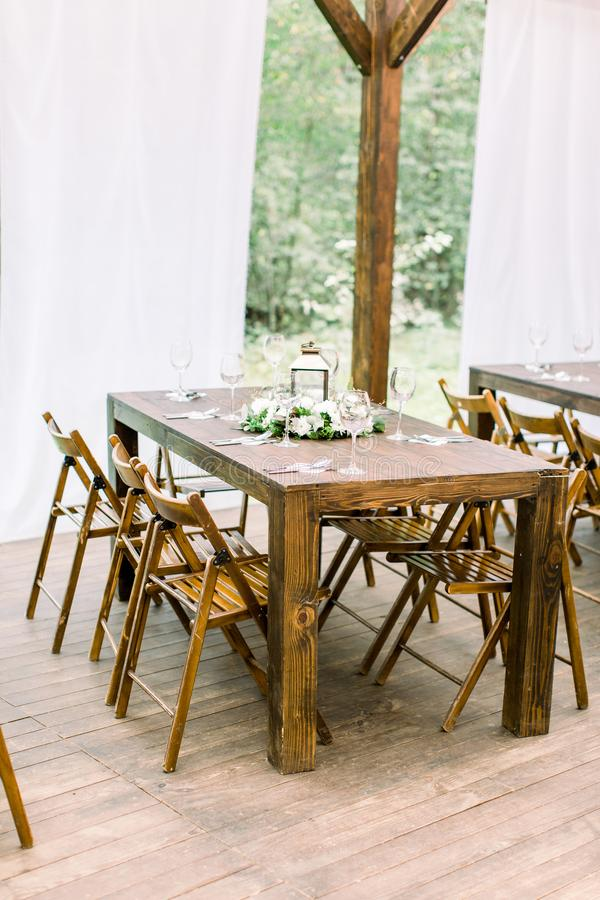 Wedding banquet wooden table in a forest or garden decorated with a composition of white flowers and greenery, lantern royalty free stock photography
