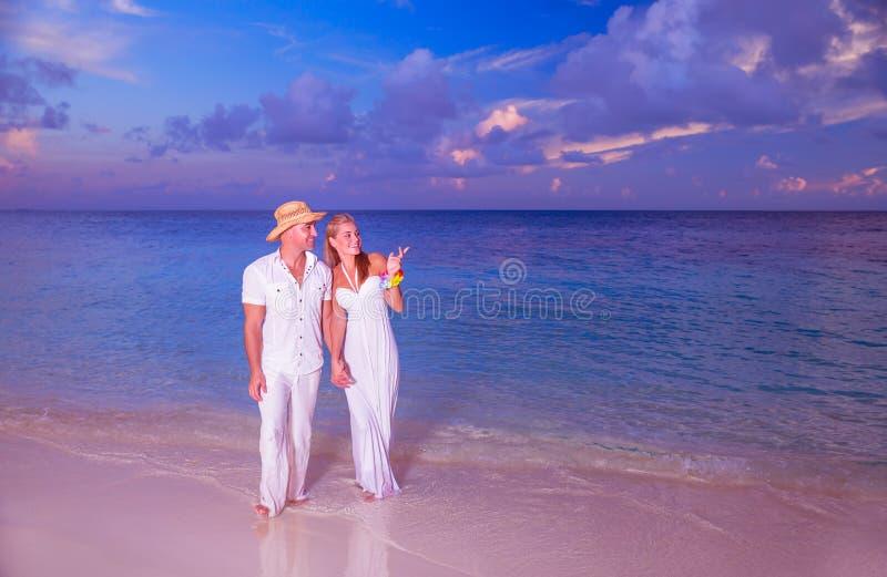 Wedding on the beach. Happy couple walking along beautiful sandy island, young family holding hands and enjoying sunset, honeymoon vacation on Maldives royalty free stock image
