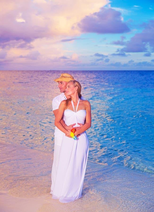 Wedding on the beach. Luxury wedding on the beach, happy romantic couple enjoying sunset on the sea, spending honeymoon vacation on Maldives islands royalty free stock image