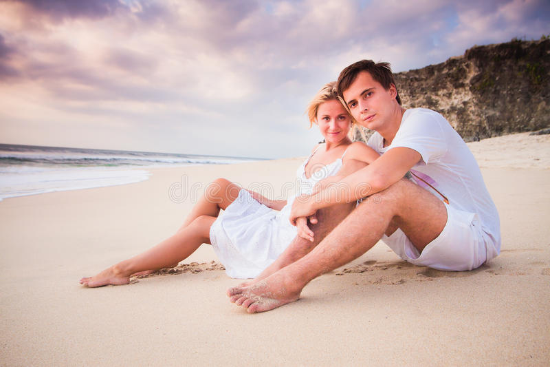 Wedding beautiful couple dressed in white sitting at the beach stock photography