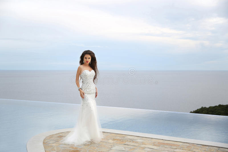Wedding. Beauty Fashion Elegant bride woman. Brunette model in l. Uxurious fashion white gown posing by infinity swimming pool over sea. outdoor portrait royalty free stock images