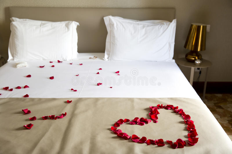 Wedding bed topped with rose petals stock photo image of - Como preparar una noche romantica ...