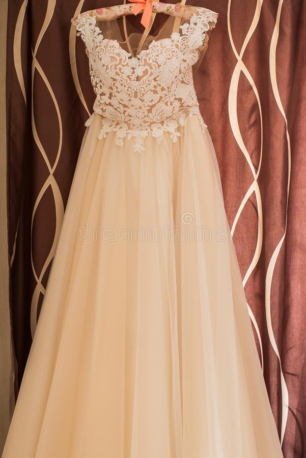 Wedding beige dress on hanger on a wall. Beautiful gown. stock photography
