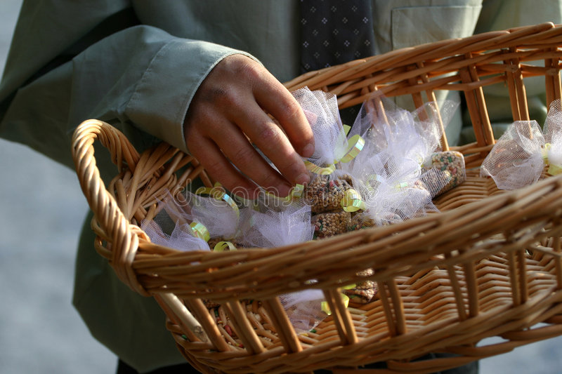 Wedding Bird Seed Throw 2. A young boy holding a basket of wrapped bird seed for the end of the wedding ceremony. Instead of rice, bird seed is used. The seeds royalty free stock photo