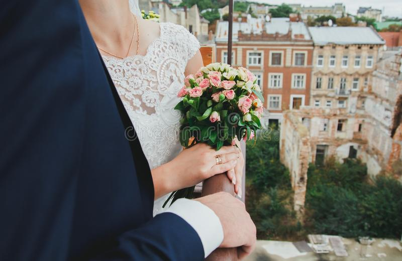 Wedding blonde couple is kissing in the ancient cafe on the roof. Groom and bride in lace satin dress are hugging over the royalty free stock photo
