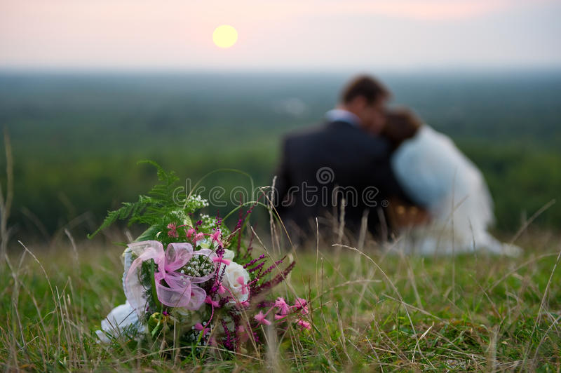 Wedding bouquet. Flowers on the grass, bride and groom siting.... shallow depth of field stock images