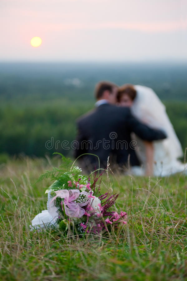Wedding bouquet. Flowers on the grass, bride and groom siting.... shallow depth of field royalty free stock images