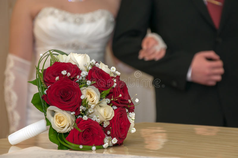 Wedding bouquet against the bride and groom