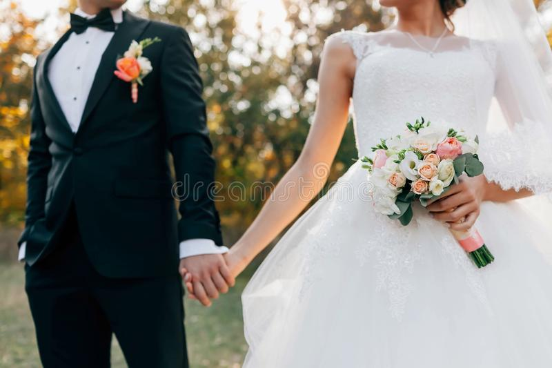 Wedding bouquet. Blurred bride with in a white dress and groom in tuxedo are holding hands. Soft focus on flowers royalty free stock photography