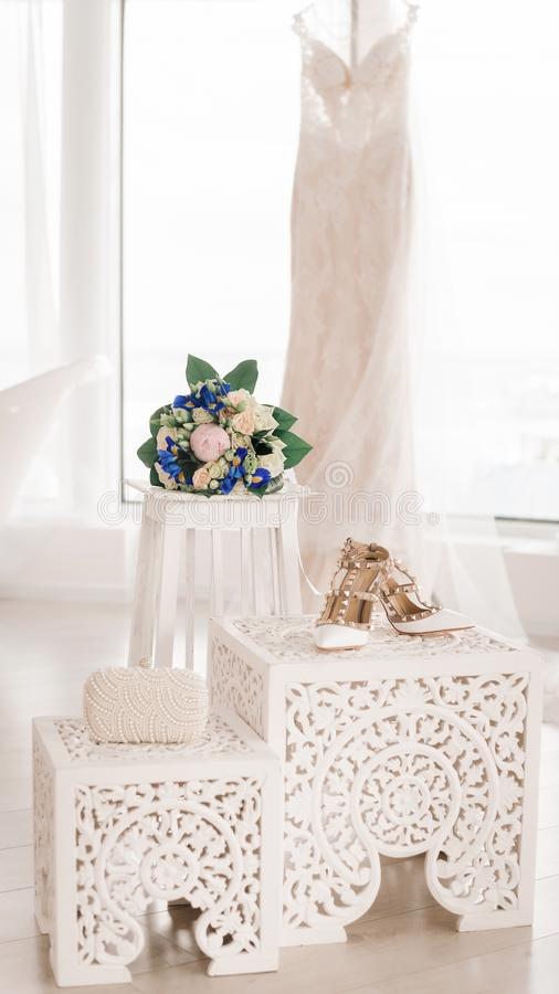 A wedding bouquet, bridal shoes and a pearl clutch stand lie against the background of a white wedding dress. Accessories for royalty free stock image