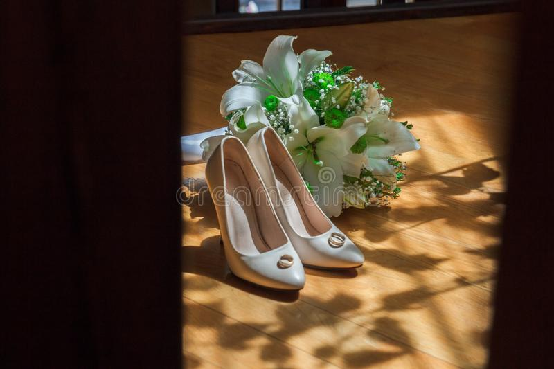Wedding bouquet, bridal shoes and wedding rings on light rays. Wedding shoes, partially illuminated by sunlight, partially in the shade royalty free stock photos