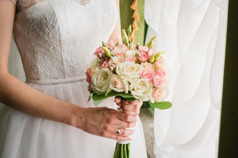 Bouquet of the bride in the hands of wedding rings stock photo