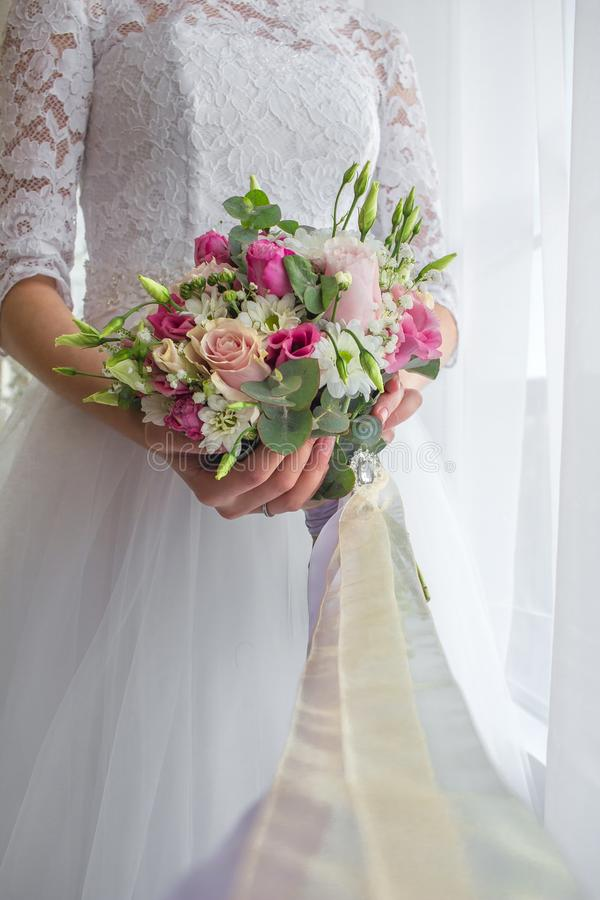 Wedding bouquet in bride& x27;s hands vertical orientation stock photos