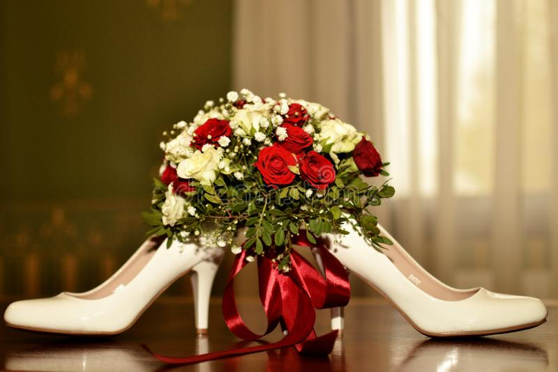 Wedding bouquet and brides shoes. On the table royalty free stock photo