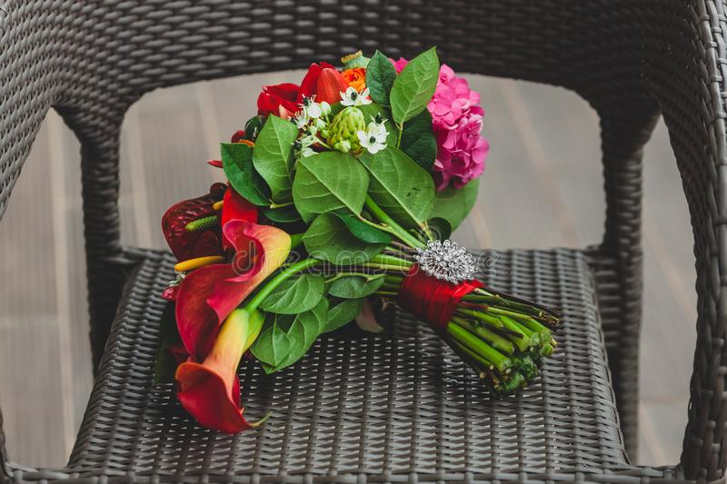 Wedding bouquet with bright red flowers and ribbon with a silver brooch on the stalk. Close-up. Artwork stock images