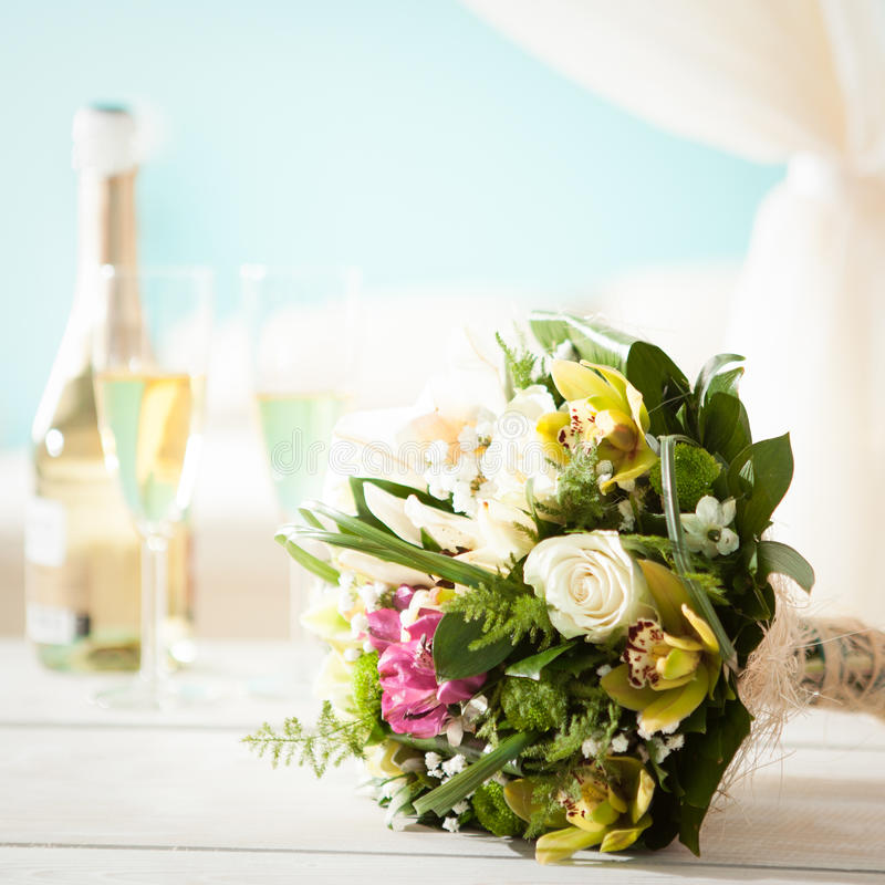 Wedding Bouquet and Champagne. Colourful wedding bouquet in front of a bottle of champagne and two flutes for the newlyweds stock photography