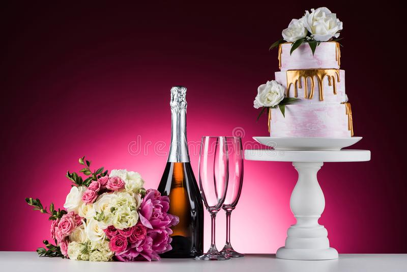 Wedding bouquet, champagne with glasses and cake on stand. On pink stock images