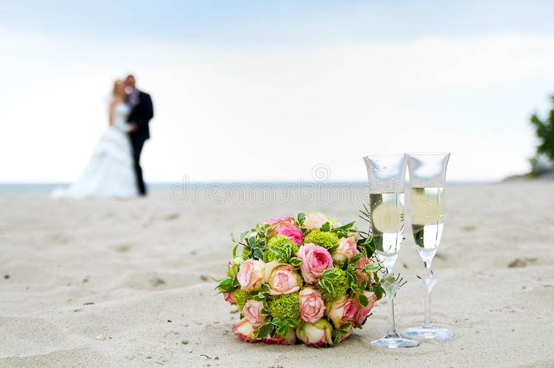 The wedding bouquet with on the beach. The wedding bouquet with a couple on the beach royalty free stock images