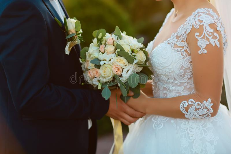 Wedding bouquet with delicate pink, beige, white flowers with green leaves in the hands of the brides in dress and costume, couple royalty free stock photography
