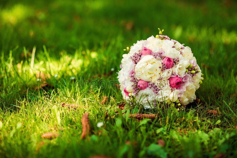 Wedding bouquet of delicate pink and white flowers lying on green grass. wedding concept stock photos