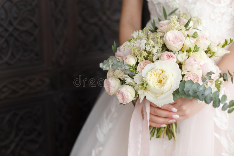 Wedding bouquet in female hands. beautiful bouquet in hand. bouquet of peonies. bouquet with roses. stock photo