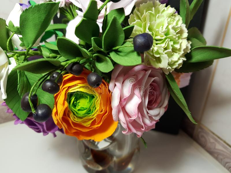 A wedding bouquet in a glass vase, flowers from the material fom multicolored and bright. royalty free stock photo