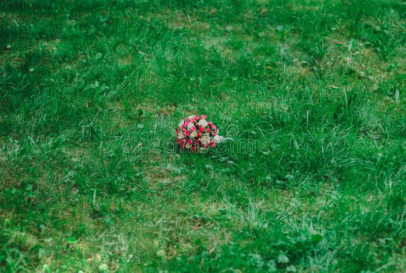 Wedding bouquet on grass. Small wedding bright pink bouquet on the emerald grass. Organic rustic and rural wedding decorative photo. Hot pink and beige flowers stock images