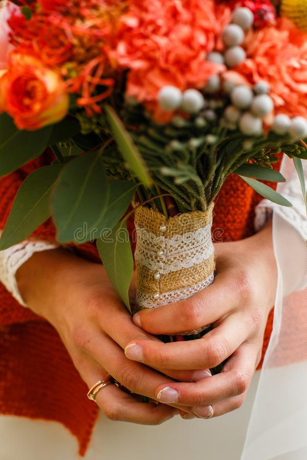 Wedding bouquet in the hands of the bride. A burgundy autumn wedding bouquet in the hands of the bride, holding, dress, calla, orange, celebration, floral royalty free stock images