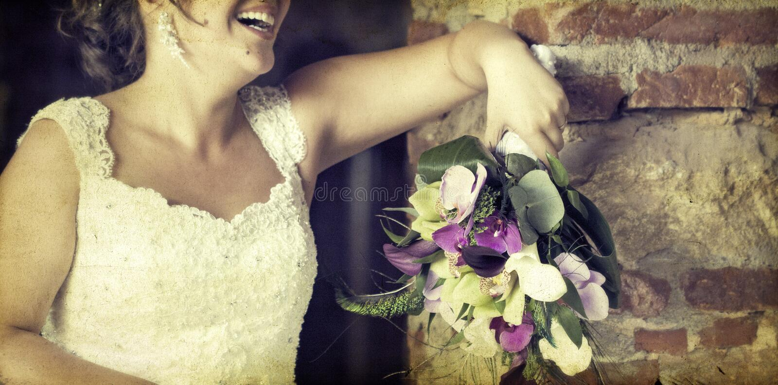 Wedding bouquet in hands of the bride. Old styled photo. Vintage photo of bride holding wedding bouquet stock photography