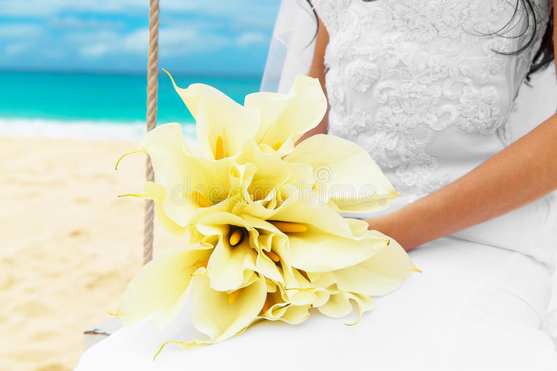 Wedding bouquet lying on the lap of the bride on a tropical beach. Blue sea in the background. Wedding bouquet lying on the lap of the bride on a tropical beach stock image