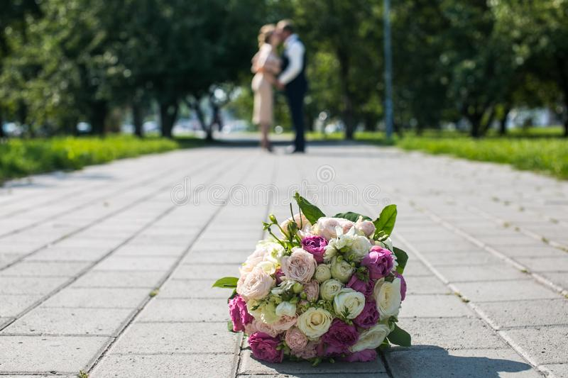 Wedding bouquet and the newlyweds in the park a beautiful wedding. Wedding bouquet and newlyweds in the background on the happiest day in a beautiful park kiss royalty free stock photo