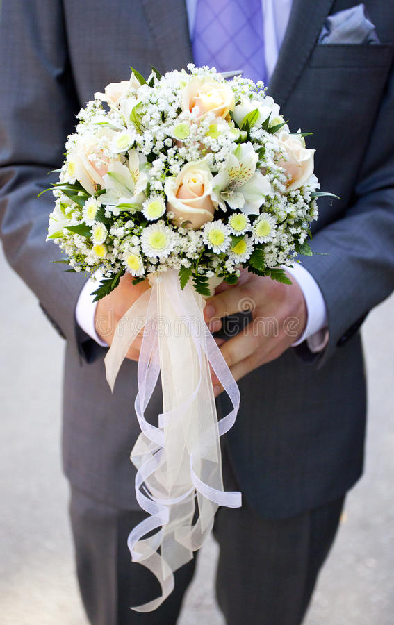 Wedding bouquet of pale pink and yellow flowers and ribbons in hands of groom royalty free stock photo
