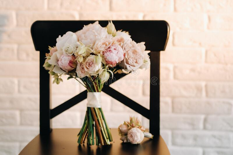 Wedding bouquet with peonies and roses on a chair and boutonniere.The decor at the wedding.  stock image
